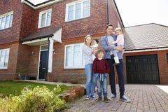 Porträt junge des Familien-stehende Außenseiten-neuen Hauses lizenzfreie stockbilder