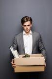 Porträt Junge feuerte tragenden Kasten des Geschäftsmannes an seinem Arbeitsplatz auf grauem Hintergrund ab Stockfoto