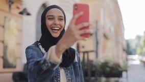 Porträt junge moslemische Frau tragenden hijab, das Videoanruf unter Verwendung der Kamera beim Reisen in der schönen Stadt hat stock footage
