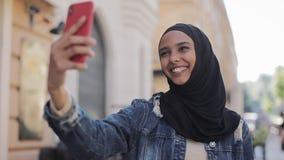 Porträt junge moslemische Frau tragenden hijab, das Videoanruf unter Verwendung der Kamera beim Reisen in der schönen Stadt hat stock video