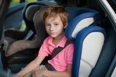 Porträt Junge sitzt in einem Autositz stockbild