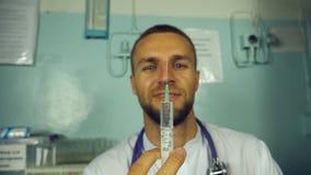 Porträt jungen männlichen kaukasischen Doktors, der eine Flüssigkeit von einer Spritze und von einem Lächeln gießt Medizinische A stock video footage