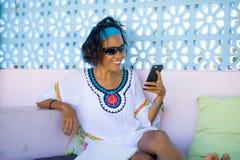 Porträt junger attraktiver und glücklicher Hippie Asiatin, die den Spaß entspannt unter Verwendung des Internet-Handys an Bett dr stockfotografie