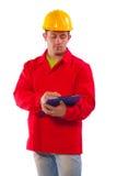 Porträt junger conctruction Arbeitskraft, die den roten Mantel lokalisiert trägt stockbild