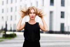 Porträt junger Dame mit dem rauhaarigen blonden Haar im Wind Stockbild