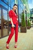Porträt junger herrlicher Dame mit dem hohen Pferdeschwanz im roten Kostüm und in den Stöckelschuhen, die vor widergespiegeltem S Stockfotografie