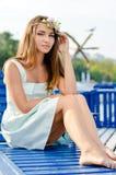 Porträt junger schöner stilvoller blonder Dame auf dem Seepier, der den Spaß aufwirft im weißen Kleid habend u. betrachtet Kamera Stockbilder