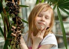 Porträt, kleines Mädchen sieben Jahre alt, sitzend nahe bei einer Palme Lizenzfreie Stockfotografie