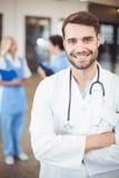 Porträt lächelnden männlichen Doktors With Arms Crossed Lizenzfreie Stockfotos