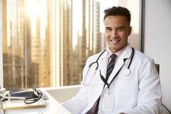Porträt lächelnden männlichen Doktors Wearing White Coat mit Stethoskop im Krankenhaus-Büro lizenzfreie stockfotografie