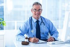 Porträt lächelnden männlichen Doktorschreibens auf Dokument in der Klinik Lizenzfreie Stockfotos