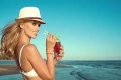 Porträt lächelnder blonder Dame des jungen Zaubers im weißen Schwimmen-BH und in trinkendem Cocktail Panamas durch ein Stroh Lizenzfreie Stockfotos
