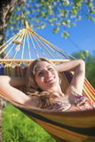 Porträt lächelnder kaukasischer blonder Dame Resting im Hügel während der Frühlings-Zeit Lizenzfreie Stockfotos
