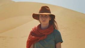 Porträt: Mädchenreisender in der Wüste auf dem Sand Tragen eines Hutes und des roten Schals Erforscht das alte Gelände und sucht stock footage