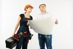 Porträt männlichen Architekten-And-Erbauer Woman Discussing-Bauplans Vorarbeiter, der Rollenpapier hält stockfotografie
