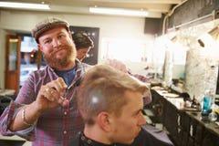 Porträt männlichen Barber Giving Client Haircut In-Shops Stockbild