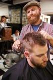 Porträt männlichen Barber Giving Client Haircut In-Shops Lizenzfreies Stockbild