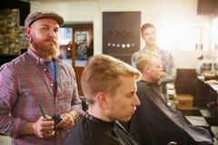 Porträt männlichen Barber Giving Client Haircut In-Shops Stockbilder