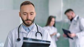Porträt männlichen männlichen Doktors mit dem Stethoskop, das Röntgenstrahlschnappschuß wiederholt stock video footage