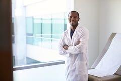Porträt männlichen Doktors Wearing White Coat im Prüfungs-Raum stockfotos