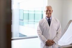 Porträt männlichen Doktors Wearing White Coat im Prüfungs-Raum lizenzfreies stockbild