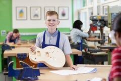Porträt männlicher hoher Schüler-Building Guitar In-Holzarbeit stockfotografie