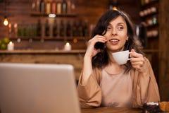 Porträt modernen Geschäft womn in einer Hippie-Kaffeestube, die am Telefon spricht und einen Tasse Kaffee hält lizenzfreie stockbilder
