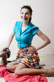 Porträt nähender schöner netter Handwerkerin junger Dame des Stoffes, die Spaß im blauen Hemd sitzt auf Boden und dem glücklichen Stockbild