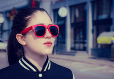 Porträt nah oben von einem stilvollen Mädchen in der roten Sonnenbrille Stockbild