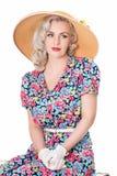 Porträt netten Retro- blonden tragenden Sonnenhutes, Sitz-, lokalisiertes O Stockfotografie