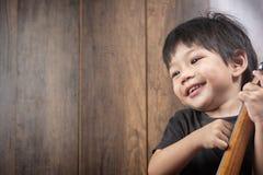 Porträt-nettes kleines asiatisches Jungen-Lächeln mit Ukulele stockfotos