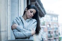 Porträt O eine junge attraktive Frau mit der Krise, die unglücklich und auf einem Balkon wertlos schaut Lizenzfreies Stockfoto
