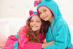 Porträt oder Schwester zwei, die sich umarmen und bathtowels mit Haube tragen lizenzfreie stockbilder