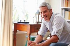 Porträt ofï ¿ ½ ein lächelnder grauer behaarter Mann, der in einem Raum sitzt Lizenzfreie Stockfotografie