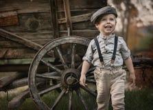 Porträt og ein kleiner Herr, der über einem hölzernen Wagen aufwirft lizenzfreie stockfotografie