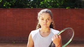 Porträt recht jungen Tennis playgirl mit dem Schläger, der an der Kamera lächelt und geht stock video
