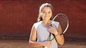 Porträt recht jungen Tennis playgirl mit dem Schläger, der an der Kamera lächelt und geht stock footage