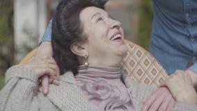 Porträt reifer Dame sitzend auf dem Rasen im Schaukelstuhl, der Sonnennahaufnahme genießt Erwachsener Enkel, der Augen von bedeck stock video footage
