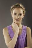 Porträt reizender blonder Dame im Purpur Lizenzfreies Stockfoto