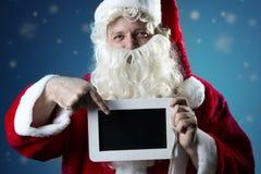 Porträt Santa Claus, die auf Schiefer zeigt Stockfotografie