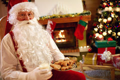 Porträt Santa Claus, die in den Plätzchen und in der Milch sitzt und genießt lizenzfreies stockbild