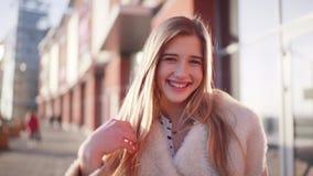 Porträt schönen Blondine, die weit zur Kamera steht nahe einem modernen Gebäude im Stadtzentrum lächeln stock video footage