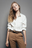 Porträt schönen Blondine in einem weißen Hemd im Studio auf einem grauen Hintergrund Lizenzfreies Stockfoto