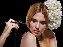 Porträt schönen jungen Blondine auf einer Dunkelheit mit Spritzpistolenmake-up Lizenzfreie Stockfotografie
