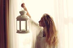 Porträt schöner blonder junger Dame, die Kerzenlichtfackel am frühen Abend hält u. Kopienraum auf hellem Fenster betrachtet Lizenzfreie Stockfotografie
