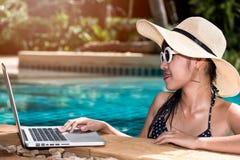 Porträt-Schönheit, die Laptop vom Swimmingpool im hote verwendet Lizenzfreies Stockfoto