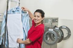 Porträt trocknenden Kleidung einer der glücklichen jungen Frau im Waschautomaten Stockbilder