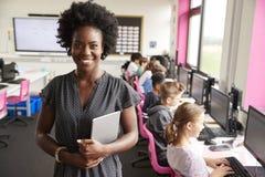 Porträt unterrichtender Linie weiblicher Lehrer-Holding Digital Tablets der hohen Schüler, die durch Schirme in der Computer-Klas stockfoto