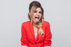 Porträt verrückter lustiger schöner Geschäftsdame mit Frisur und Make-up im roten fantastischen Blazer, stehend mit der Zunge her stockfotos