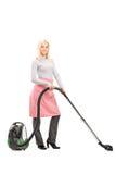 Porträt in voller Länge einer blonden Hausfraureinigung mit einem Vakuum Stockfotografie